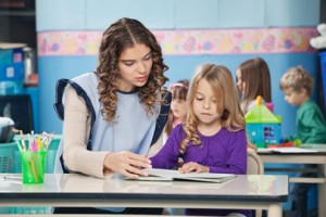 Teacher And Girl Reading Book With Children In Background