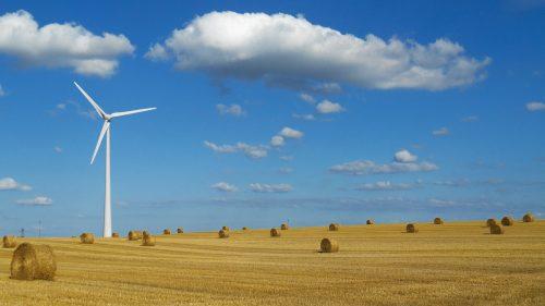 Une éolienne installée dans un champ avec des bottes de paille