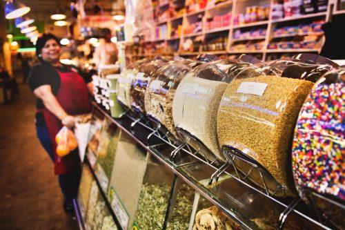 employé de supermarché en arrière-plan d'un stand de produits en vrac