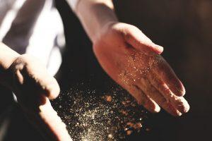 boulanger qui tape ses mains avec de la farine